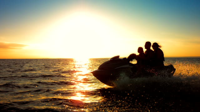 slo mo family riding a jet boat at sunset - jet ski stock videos & royalty-free footage