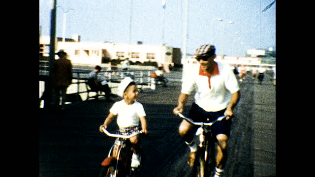 """vidéos et rushes de family riding bicycle on beach boardwalk with lots of people and stores; pier with building """"atlantic city beach patrol""""; boy playing inside hotel... - allée couverte de planches"""