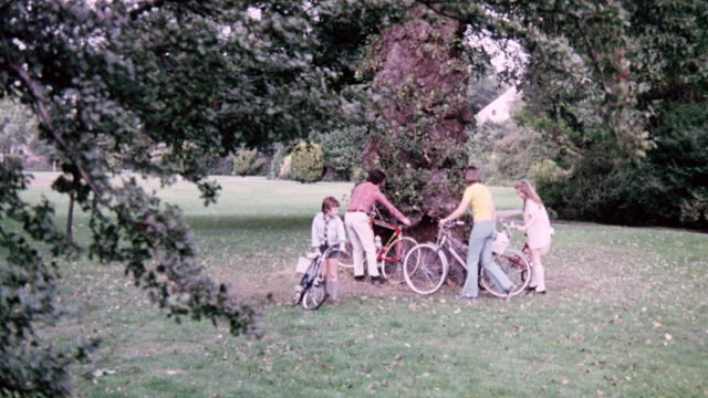 1974 montage a family riding bicycles, leaning them against a tree, and setting up a picnic in the park / united kingdom - son stock videos & royalty-free footage