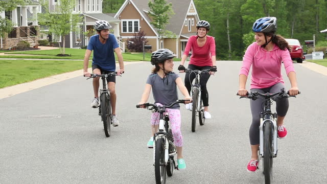 family riding bikes in suburban neighborhood - cycling helmet stock videos & royalty-free footage