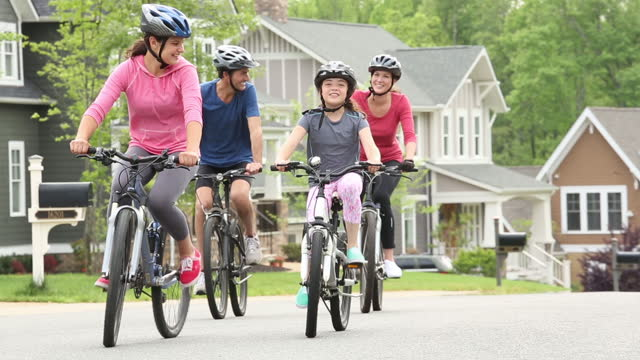 family riding bikes in suburban neighborhood