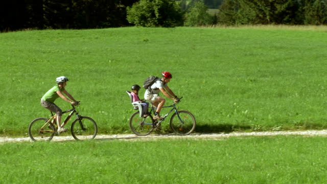 hd: family riding bikes in the countryside - bicycle seat stock videos & royalty-free footage