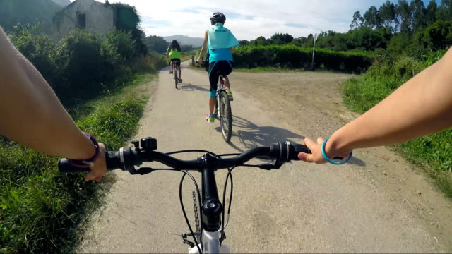 family riding bikes on a thin road in nature. - riding stock videos & royalty-free footage