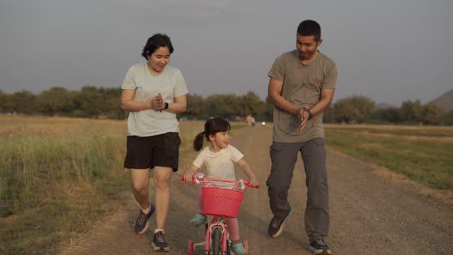 stockvideo's en b-roll-footage met de berijdende fietsen van de familie op zonnige de zomerdag - sunny