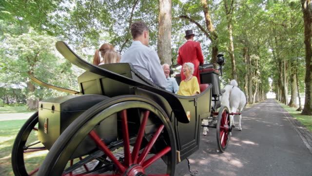SLO MO-TS Familie Reiten durch park in der Pferdekutsche