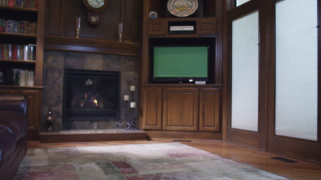Family room den featuring a burning fireplace and green screen television.