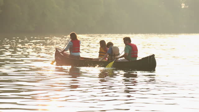 Family rowing canoe in river