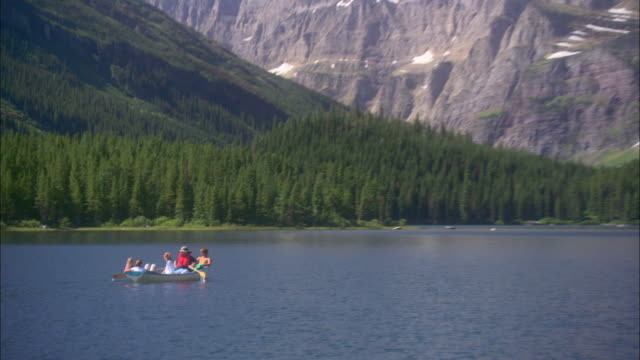 stockvideo's en b-roll-footage met a family rows a rowboat across a mountain lake in glacier national park, montana. - montana westelijke verenigde staten