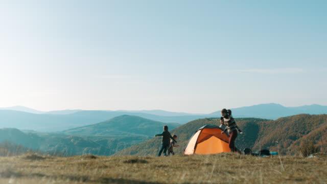 山の上にテントの周りを実行している家族 - camping点の映像素材/bロール