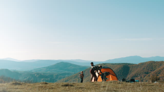family running around tent on top of the mountain - camping stock videos & royalty-free footage