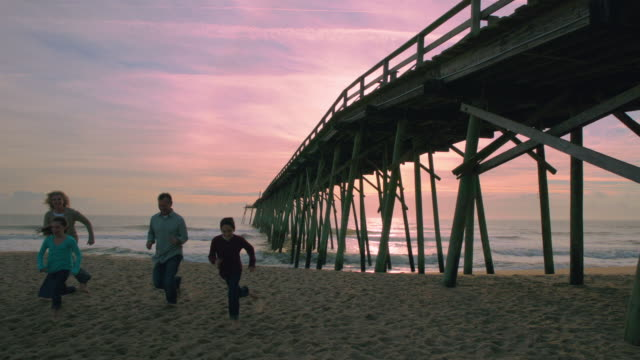 family running from shore together (slo-mo) - wilmington north carolina stock-videos und b-roll-filmmaterial