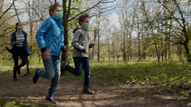 family running in forest during covid-19 pandemic - natural parkland stock videos & royalty-free footage