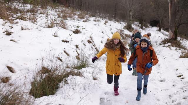vidéos et rushes de fonctionnement de famille dans la nature d'hiver - vêtement chaud