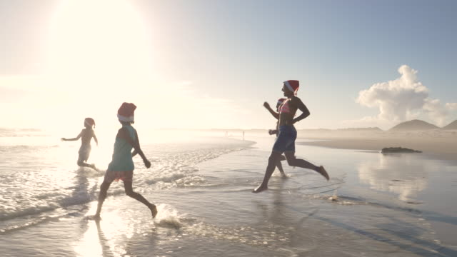 Family running into the sea in Santa hats