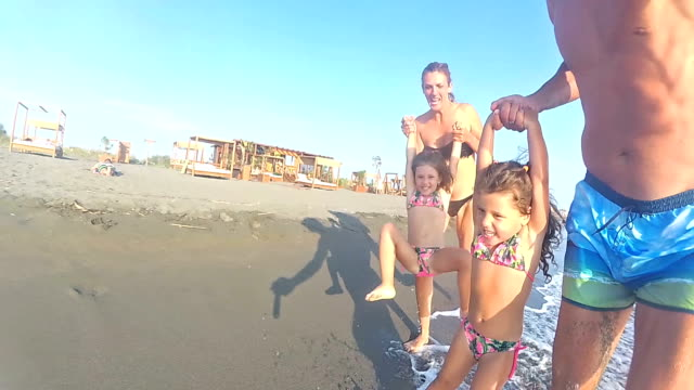 slo mo family running on the beach at sunset and having fun - mediterranean sea stock videos & royalty-free footage