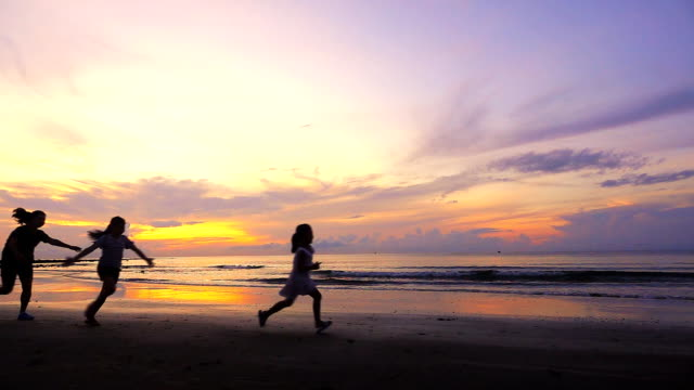 family running on the tropical beach, slow motion - in silhouette stock videos & royalty-free footage