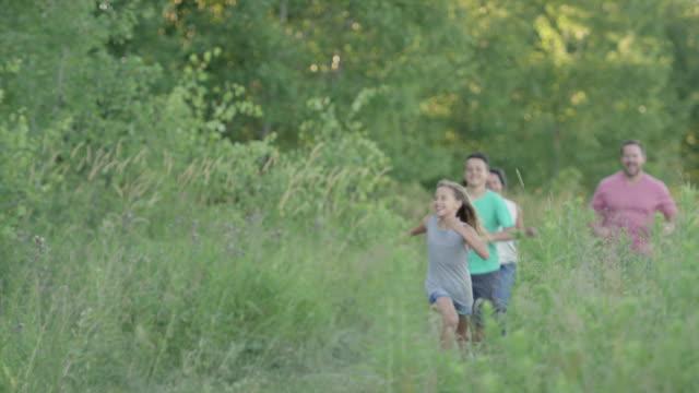 vídeos de stock, filmes e b-roll de família correr juntos ao ar livre - brincadeira de pegar