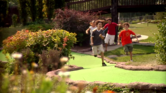 family running up mini golf course to get to next shot - minigolf stock-videos und b-roll-filmmaterial