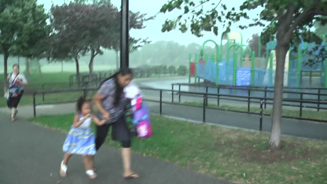 a family runs for shelter as a sudden thunderstorm hits with little warning and heavy rain begins to fall - emergency shelter stock videos & royalty-free footage