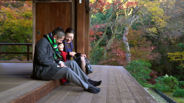 Family sat outside at a temple having fun together