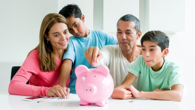 vídeos de stock e filmes b-roll de family saving money in a piggybank - latin american and hispanic ethnicity