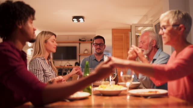 vídeos de stock e filmes b-roll de family saying grace before enjoying meal at home together - benção