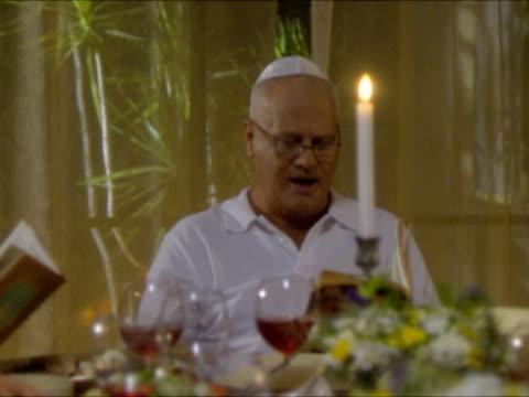 ms cu pan r/f family saying prayer sitting at dinner table at seder night during passover / beit yitzhak, israel - 30 34 ��r bildbanksvideor och videomaterial från bakom kulisserna