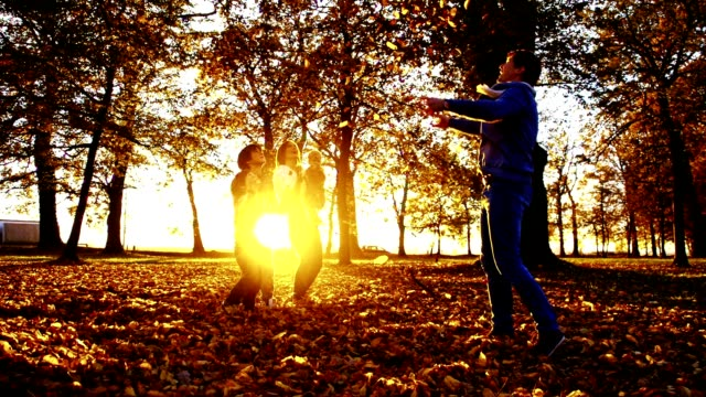 slo mo family scattering leaves at dusk - family with three children stock videos & royalty-free footage