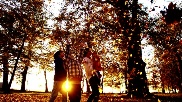 slo mo family scattering leaves at sunset - family with three children stock videos & royalty-free footage