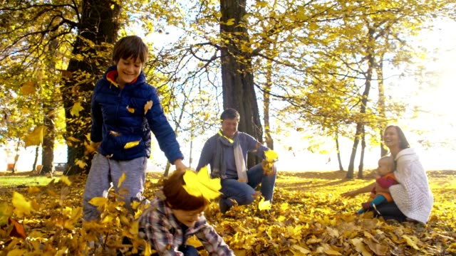 slo mo family scattering leaves over each others - family with three children stock videos & royalty-free footage