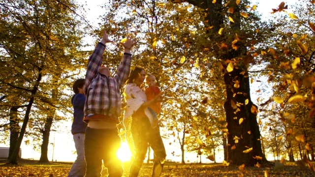 slo mo family scattering leaves over themselves - family with three children stock videos & royalty-free footage