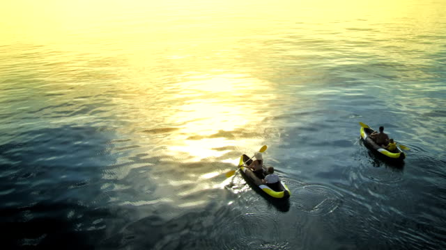 aerial family sea kayaking at sunset - canoe stock videos & royalty-free footage