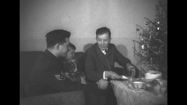 vídeos de stock e filmes b-roll de a family seated around a christmas tree as the man cuts a cake woman and little boy look on he hands a slice to a man in a uniform / the boy chews on... - chávena de chá