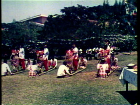 1953 WS MS Family serve themselves food from long table, Young people dance the tinikling with long bamboo sticks / Philippines / AUDIO