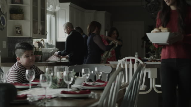 family setting table for holiday meal in domestic kitchen / orem, utah, united states - orem stock videos & royalty-free footage