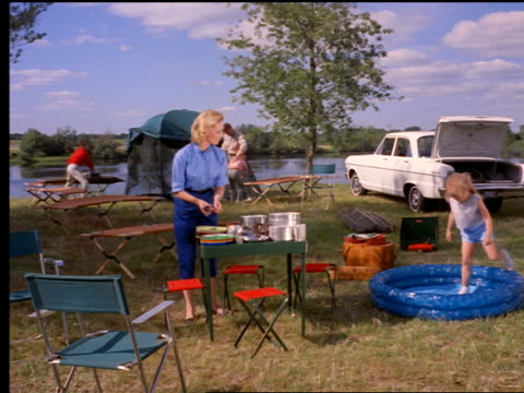 1962 family setting up campsite with cookware, tent + inflatable swimming pool next to water