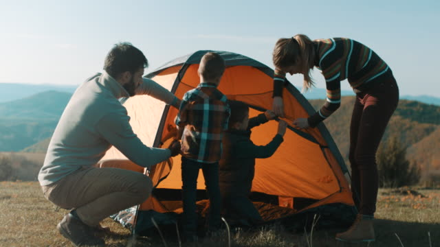family setting up tent on top of the mountain - tent stock videos & royalty-free footage