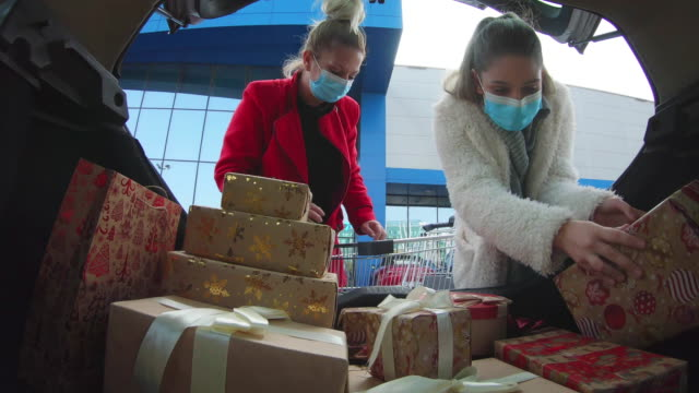 family shopping christmas gifts during covid-19 pandemic. they wears a protective mask to protect from coronavirus covid-19. - gift box stock videos & royalty-free footage