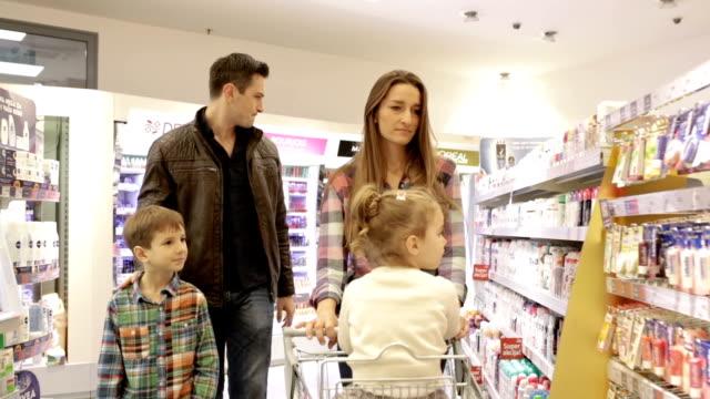 Family shopping in supermarket, panning shot