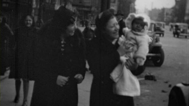 a family shows off a baby while walking down a new york street various classic cars drive by in the background - 1928 stock videos & royalty-free footage