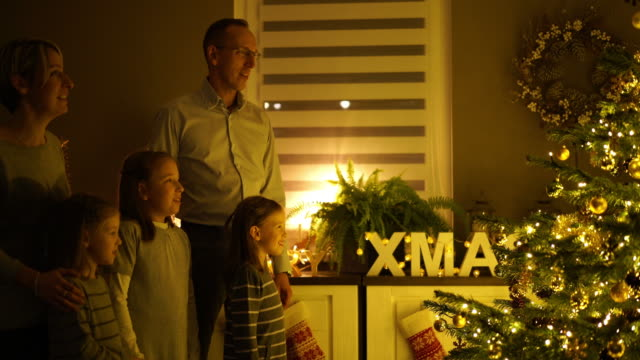 family singing at christmas tree - familie mit drei kindern stock-videos und b-roll-filmmaterial