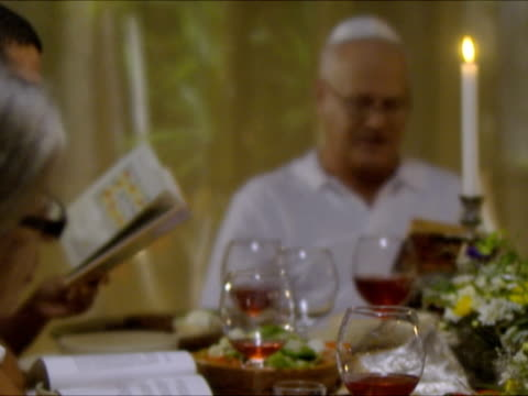 ms cu pan r/f family singing from prayer book, sitting at dinner table at seder night during passover / beit yitzhak, israel - passover stock videos and b-roll footage