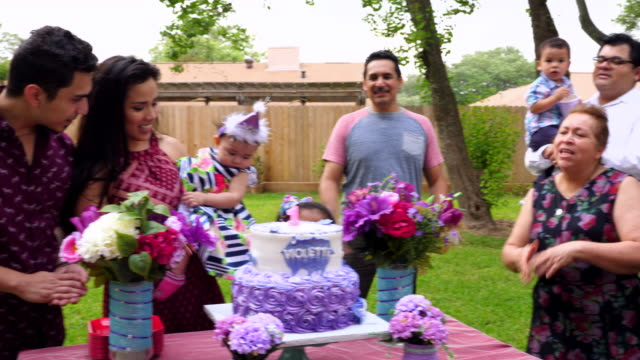 MS PAN Family singing happy birthday in backyard to young girl on first birthday