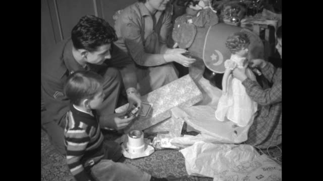 family sits at christmas tree, with father smoking and woman looking on as us soldier helps children open presents that he brought the family as he... - 西ドイツ点の映像素材/bロール