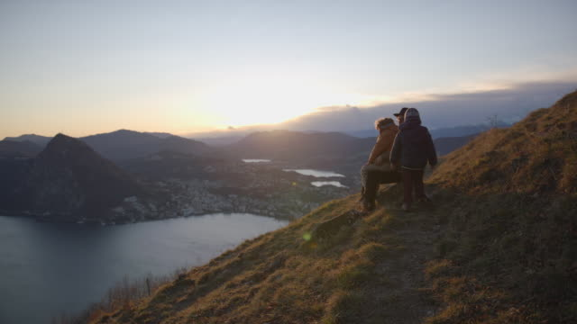 family sits at view point over lake, watching sunset together - woolly hat stock videos & royalty-free footage