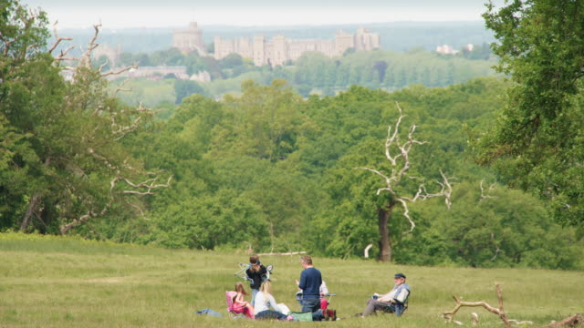 a family sits on the grass in the spring sunshine in windsor great park with a picnic with windsor castle in the background on may 17 2020 in... - getting away from it all stock videos & royalty-free footage