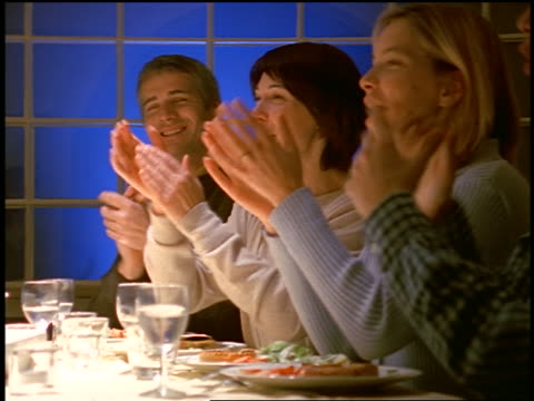 family sitting around dining room table applauding at something offscreen in evening - matrum bildbanksvideor och videomaterial från bakom kulisserna