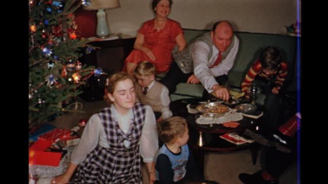 1957 home movie family sitting around enjoying christmas together / toronto, canada - 1957 bildbanksvideor och videomaterial från bakom kulisserna
