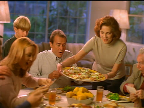 vidéos et rushes de family sitting at dinner table looking at photos / woman serves tostadas + they get excited - 1990 1999