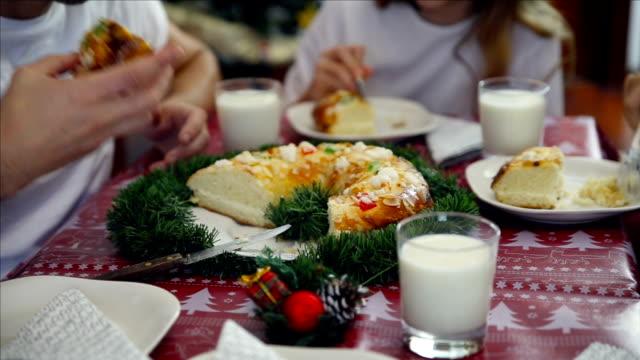 vídeos y material grabado en eventos de stock de family sitting at dinner table talking, laughing and eating roscón de reyes in christmas time - reyes magos